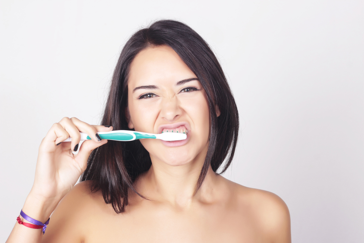 Young woman brushing her teeth isolated over white background